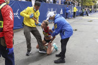 Madeleine Rouse of Plano, Texas gets assistance after finishing the 125th Boston Marathon on Monday, Oct. 11, 2021, in Boston. (AP Photo/Winslow Townson)