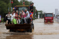 Rescuers evacuate people from a flooded area in Weihui in central China's Henan Province, Monday, July 26, 2021. Residents laid flowers on Tuesday at the entrance of a subway station where more than a dozen people died after a record-breaking downpour flooded large swaths of Henan province in central China. (Chinatopix via AP)