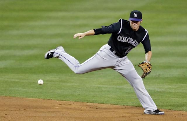 Colorado Rockies shortstop Josh Rutledge can't manage a flip throw to second trying to get the force out after fielding a grounder behind second base hit by Abraham Almonte in the second inning of a baseball game Tuesday, Aug. 12, 2014, in San Diego. (AP Photo/Lenny Ignelzi)
