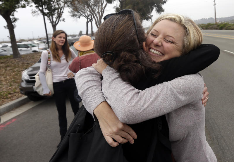 Chrystal Coleman, right, hugs Laurie Headrick near the gate to the San Onofre nuclear power plant, as they wait for the beginning of a news conference held by opponents of the plant Friday, June 7, 2013, in San Onofre, Calif. The troubled power plant on the California coast is closing after an epic 16-month battle over whether the twin reactors could be safely restarted with millions of people living nearby, officials announced Friday. (AP Photo/Gregory Bull)