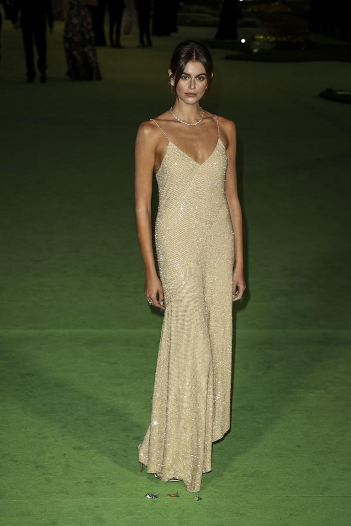 A woman in a sparkly gold dress posing on a green carpet