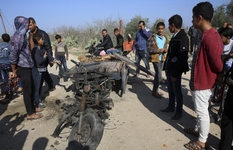 FILE - In this Monday, Nov. 12, 2018 file photo, Palestinians inspect a vehicle that was destroyed in an Israeli raid that killed seven Hamas Palestinian militants, including a local Hamas commander, late Sunday, east of Khan Younis, southern Gaza Strip. An Israeli army officer was also killed in the incurison into Gaza. The fighting came just days after Israel and Hamas reached indirect deals, backed by Qatar and Egypt, to allow cash and fuel into Gaza. A month after a heavy round of Israel-Hamas fighting, the undercover Israeli operation that sparked the battle remains clouded in mystery(AP Photo/Adel Hana, File)
