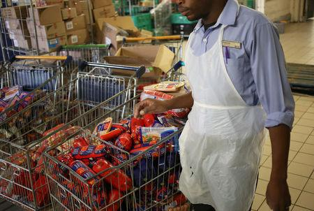 """A worker walks past cold meat products know as """"polony"""" after it was removed from the shelves of Pick n Pay Store in Johannesburg, South Africa, March 5, 2018. REUTERS/Siphiwe Sibeko"""