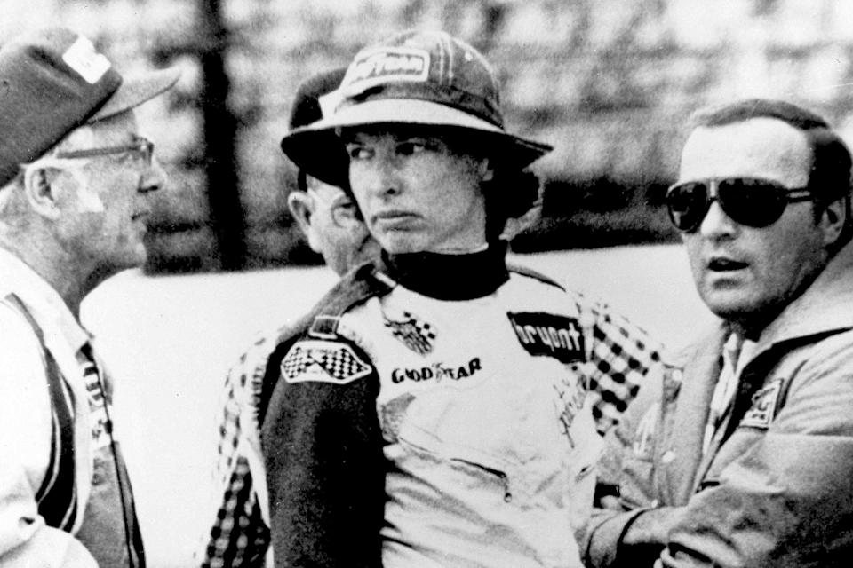 FILE - In this May 23, 1976, file photo, Janet Guthrie talks to racing car owner-builder Rolla Vollstedt, left, and A.J. Foyt, right, in the pits of the Indianapolis Motor Speedway, in Indianapolis. Janet Guthrie is still astonished at all the fan mail that pours in from around the world. And she's honored to hear that Academy Award winner Hilary Swank wants to portray her in a movie. (AP Photo/File)