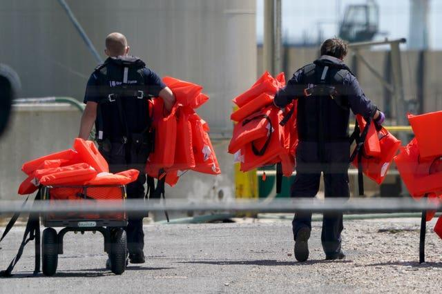 Life vests used by people thought to be migrants are taken away by Border Force officers for disposal in Dover, Kent (Gareth Fuller/PA)