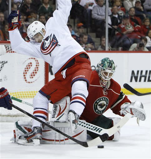Columbus Blue Jackets left wing Nick Foligno, left, lands on Minnesota Wild goalie Niklas Backstrom (32), of Finland, ad Backstrom stops a shot during the second period of an NHL hockey game in St. Paul, Minn., Saturday, April 13, 2013. (AP Photo/Ann Heisenfelt)