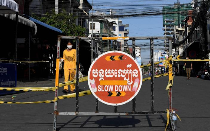 A woman carries food along a street past a barricade set up in a neighbourhood due to lockdown restrictions introduced to try to halt a surge in cases of the Covid-19 coronavirus in Phnom Penh - TANG CHHIN SOTHY / AFP