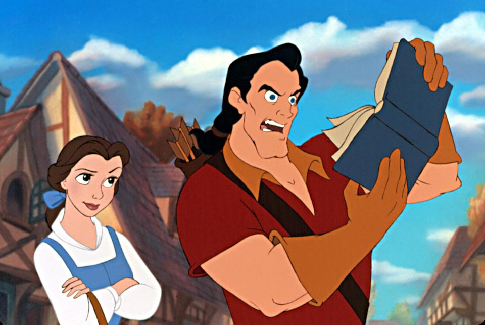 Gaston is puzzled by a book while Belle looks on