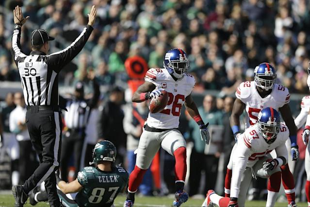 New York Giants strong safety Antrel Rolle (26) celebrates while running away from Philadelphia Eagles tight end Brent Celek (87) after intercepting a pass during the first half of an NFL football game on Sunday, Oct. 27, 2013, in Philadelphia. (AP Photo/Matt Rourke)