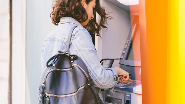 Woman using credit card withdrawing money from an ATM machine outside a branch of savings bank.