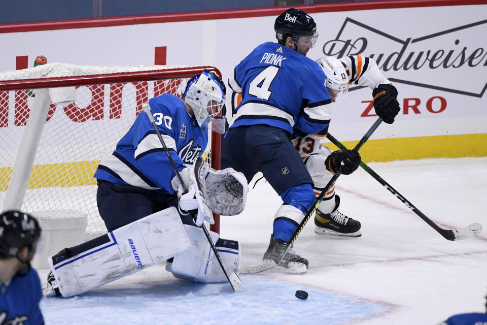 Winnipeg Jets goaltender Laurent Brossoit (30) makes a save on Edmonton Oilers' Jesse Puljujarvi (13) as Neal Pionk (4) defends during the second period of an NHL hockey game, Sunday, Jan. 24, 2021 in Winnipeg, Manitoba. (Fred Greenslade/The Canadian Press via AP)