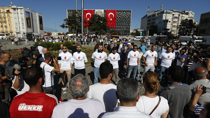 """Men face people that gathered for a silent protest at Taksim Square in, Istanbul, Turkey, Wednesday, June 19, 2013. After weeks of sometimes-violent confrontation with police, Turkish protesters have found a new form of resistance: standing still and silent. T-shirt reads """"Against Standing Man."""" (AP Photo/Petr David Josek)"""