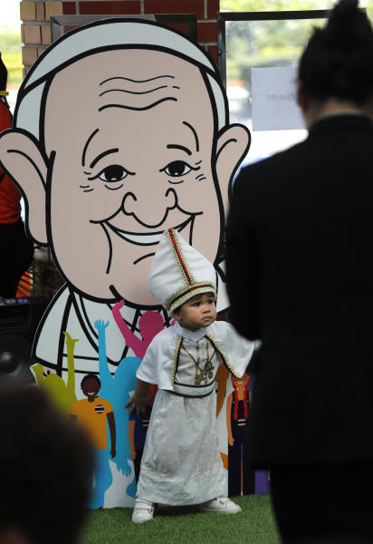 A child dressed as the Pope stands in front of a caricature of Pope Francis at Saint Louis Hospital in Bangkok, Thailand, Thursday, Nov. 21, 2019. Pope Francis called for migrants to be welcomed and for women and children to be protected from exploitation, abuse and enslavement as he began a busy two days of activities in Thailand on Thursday. (AP Photo/Manish Swarup)