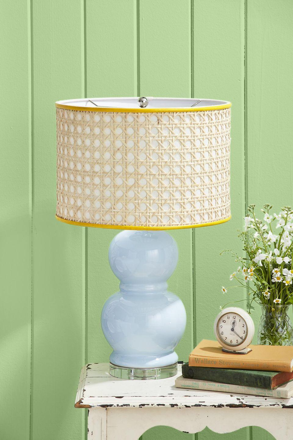 <p>This easy upgrade to a drum-shaped lampshade add loads of texture and a bright pop of color to any room.<strong><br></strong></p><p><strong>To make: </strong>Cut a piece of caning to the height and circumference of a drum-shaped lamp shade. Spray the back of the caning with adhesive spray, such as Super 77; attach to shade. Cut two pieces of flat reed to the diameter of the shade; paint desired color. Once dry, attach with hot-glue.</p>