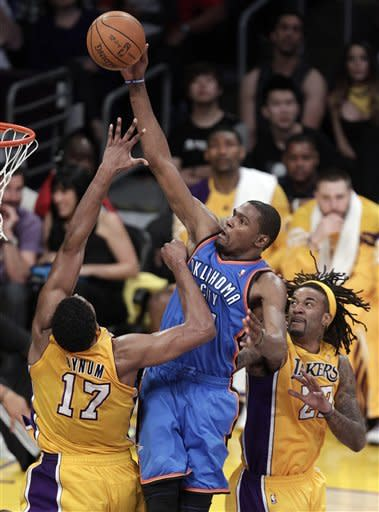 Oklahoma City Thunder's Kevin Durant, center, goes up for a basket as he is defended by Los Angeles Lakers' Andrew Bynum, left, and Jordan Hill during the second half in Game 4 of an NBA basketball playoffs Western Conference semifinal in Los Angeles, Saturday, May 19, 2012. (AP Photo/Jae C. Hong)