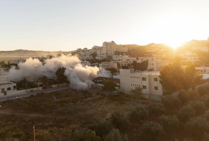 The sun rises while an Israeli army unit demolishes the house of Palestinian American Muntasser Shalaby using controlled explosions, in the West Bank village of Turmus Ayya, north of Ramallah, Thursday, July. 8, 2021. Israeli forces on Thursday demolished the family home of Shalaby who is accused of being involved in a deadly attack on Israelis in the West Bank in May. (AP Photo/Nasser Nasser)