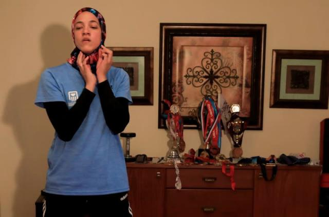 Egyptian Taekwondo practitioner Wahba dons a sports hijab next to her trophies and medals at her homein Cairo