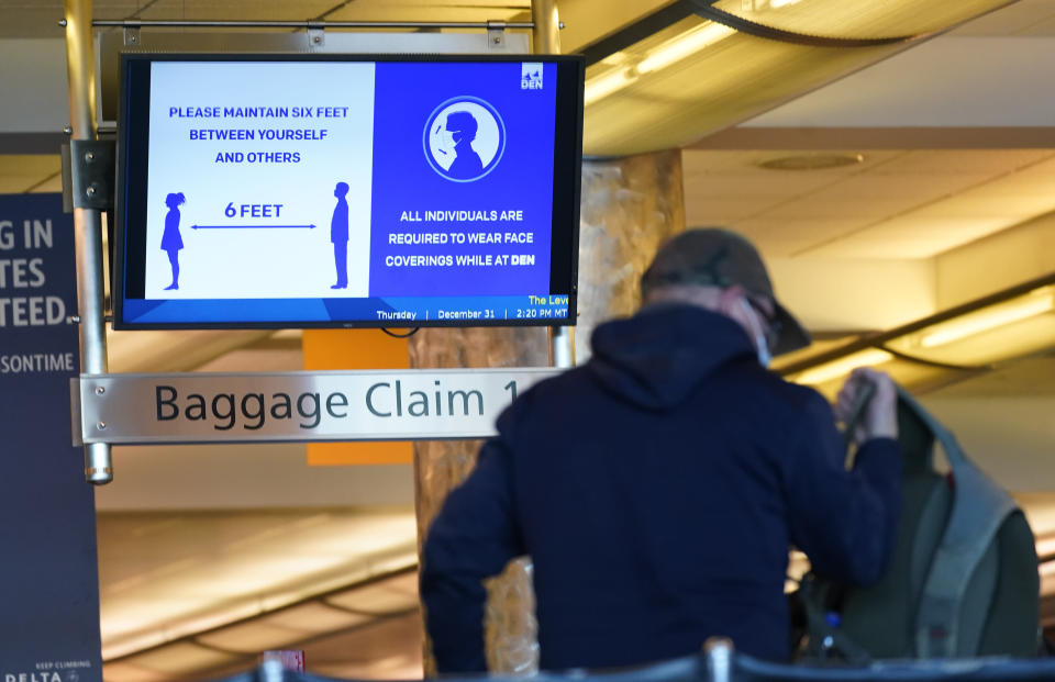 """FILE - In this Thursday, Dec. 31, 2020 file photo, an electronic sign advises travelers to wear face masks and practice social distancing while passing through the main terminal of Denver International Airport in Denver. On Friday, April 9, 2021, The Associated Press reported on stories circulating online incorrectly asserting the federal government wants to require Americans to present a health passport or vaccine certificate """"on demand,"""" including for domestic travel. While private businesses are considering vaccine passports for certain activities, Biden administration officials have said the federal government will not mandate vaccine passports. (AP Photo/David Zalubowski)"""