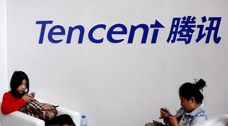 FILE PHOTO: Visitors use phones underneath of logo of Tencent at Global Mobile Internet Conference in Beijing
