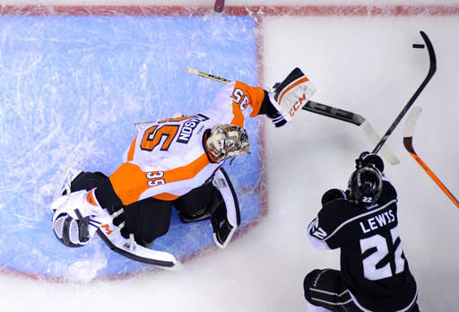 Los Angeles Kings center Trevor Lewis, right, tries to get a shot in on Philadelphia Flyers goalie Steve Mason during the first period of an NHL hockey game, Saturday, Feb. 1, 2014, in Los Angeles. (AP Photo/Reed Saxon)