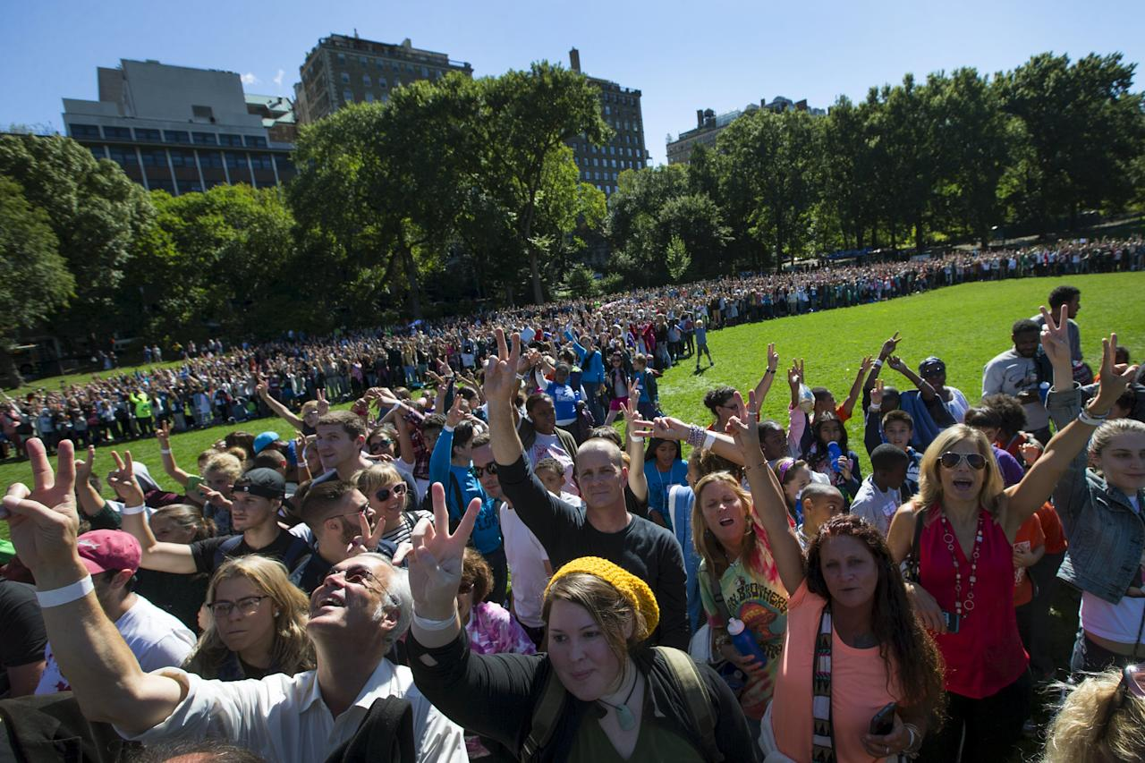 People show the peace sign as they gather to form a giant peace symbol on the East Meadow of New York's Central Park, October 6, 2015. Organized by Yoko Ono to celebrate the 75th anniversary of John Lennon's birth, thousands took part in the event in an attempt to break the Guinness World Record for the largest human peace sign.  REUTERS/Mike Segar      TPX IMAGES OF THE DAY