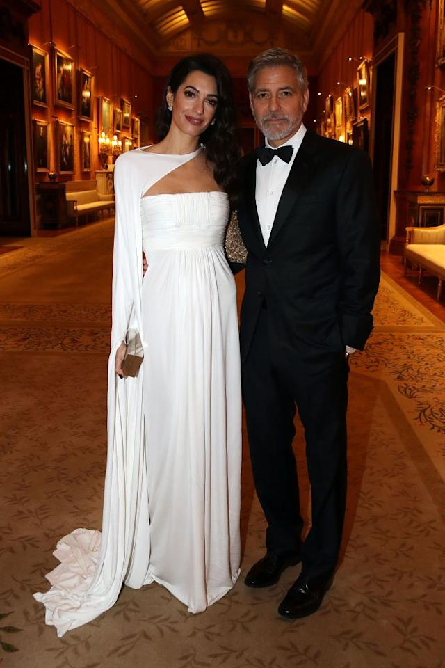 <p>Amal and George Clooney dressed up for a dinner celebrating the Prince's Trust at Buckingham Palace. Amal wore stunning white gown with an asymmetrical neckline to the event, which was hosted by Prince Charles.</p>