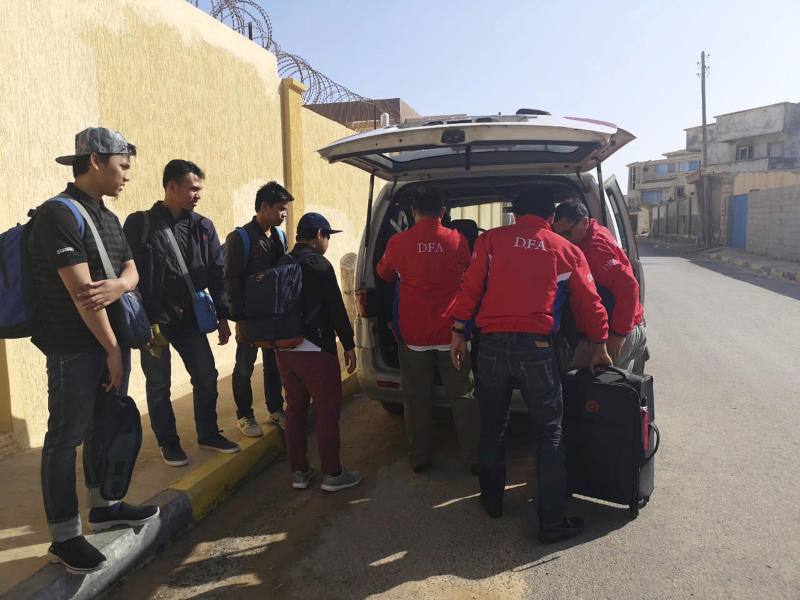 In this Wednesday, April 17, 2019, photo released by the Department of Foreign Affairs, Filipinos are assisted by staff of the department as they are evacuated from Tripoli, Libya. Philippine diplomats started evacuating a small group of Filipinos from the Libyan capital after it was hit by a barrage of rocket fire that wounded one Filipino, officials said Thursday, April 18, 2019. (Department of Foreign Affairs via AP)