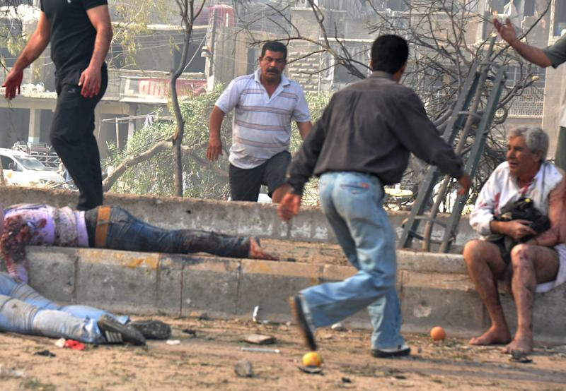 In this photo released by the Syrian official news agency SANA, men run between dead and injured people at the scene where two bombs exploded in the Qazaz neighborhood in Damascus, Syria, Thursday, May 10, 2012. Two large explosions ripped through the Syrian capital Thursday, heavily damaging a military intelligence building and leaving blood and human remains in the streets. (AP Photo/SANA)