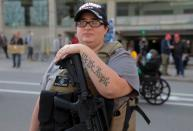 A woman carries a weapon as supporters of U.S. President Donald Trump protest the election outside the TCF Center in Detroit