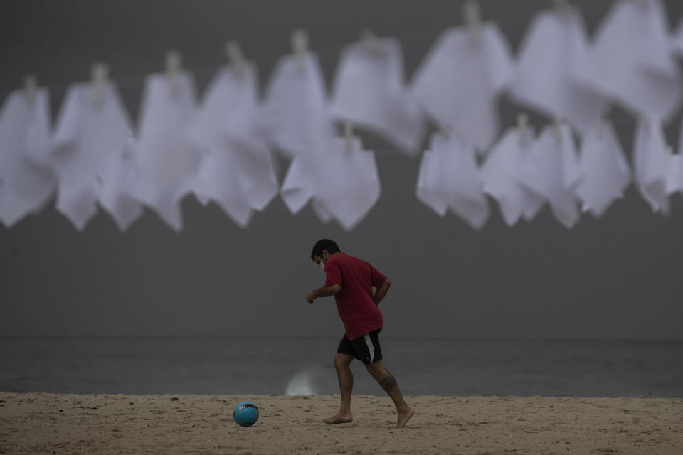"""A man kicks a ball on Copacabana beach past white flags hanging on clotheslines that represent people who have died of COVID-19 in Rio de Janeiro, Brazil, Friday, Oct. 8, 2021. The action was organized by the NGO """"Rio de Paz"""" to protest the government's handling of the pandemic as the country nears a total of 600,000 COVID-19 related deaths. (AP Photo/Bruna Prado)"""