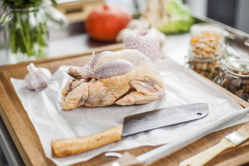 A photo of a raw whole chicken on a chopping board about to be roasted.