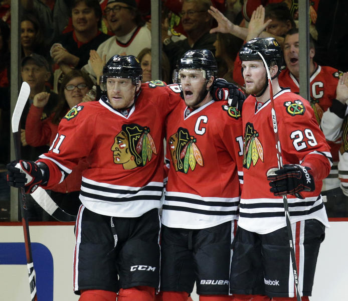 Chicago Blackhawks' Jonathan Toews, center, celebrates with Marian Hossa, left, and Bryan Bickell after scoring his goal against the Los Angeles Kings during the third period of Game 1 of the Western Conference finals in the NHL hockey Stanley Cup playoffs in Chicago on Sunday, May 18, 2014. The Blackhawks won 3-1. (AP Photo/Nam Y. Huh)