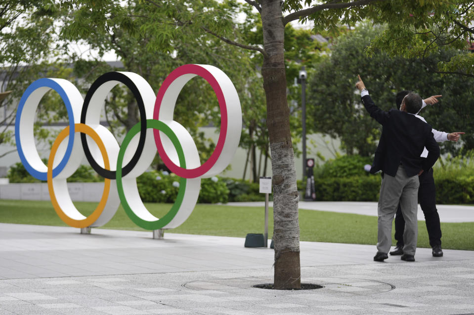 FILE - In this June 2, 2021, file photo, men gesture near the Olympic Rings, in Tokyo. Public sentiment in Japan has been generally opposed to holding the Tokyo Olympics and Paralympics. This is partly based of fears the coronavirus will spike as almost 100,000 people — athletes and others — enter for both events.(AP Photo/Eugene Hoshiko, File)