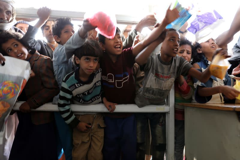 People crowd to get food rations from a charity kitchen in Sanaa