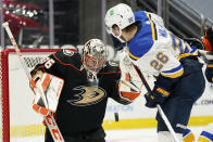 Anaheim Ducks goaltender John Gibson, left, stops a shot as St. Louis Blues left wing Nathan Walker watches during the first period of an NHL hockey game Monday, March 1, 2021, in Anaheim, Calif. (AP Photo/Mark J. Terrill)