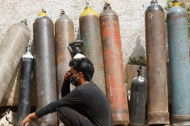 A man waits outside a factory to get his oxygen cylinder refilled, amidst the spread of the coronavirus disease in New Delhi, India.