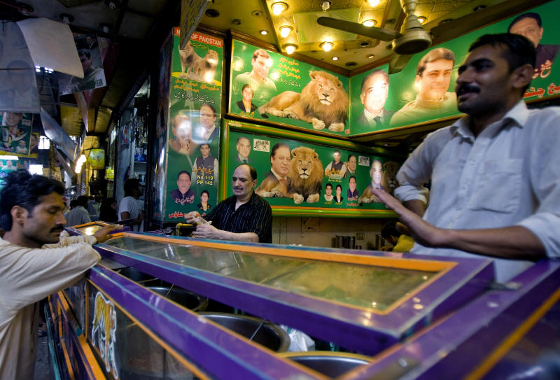 A Pakistani vendor talks with a customer at a shop decorated with the pictures of former prime minister and Pakistan Muslim League-N party chief Nawaz Sharif and other party leaders in downtown Lahore, Pakistan, Sunday, May 12, 2013. Sharif declared victory following a historic election marred by violence Saturday, a remarkable comeback for a leader once toppled in a military coup and sent into exile. (AP Photo/Anjum Naveed)
