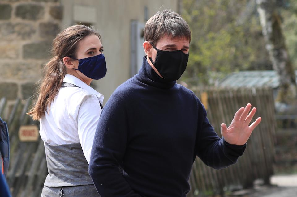 Actor Tom Cruise waves to onlookers as he walks to the set of his latest project, which is filming in the sidings of the railway station in the village of Levisham in the North York Moors. Picture date: Tuesday April 20, 2021.