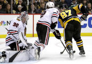 Chicago Blackhawks goaltender Cam Ward (30) stops a shot by Pittsburgh Penguins' Sidney Crosby (87) with Duncan Keith (2) defending during the second period of an NHL hockey game in Pittsburgh, Sunday, Jan. 6, 2019. (AP Photo/Gene J. Puskar)