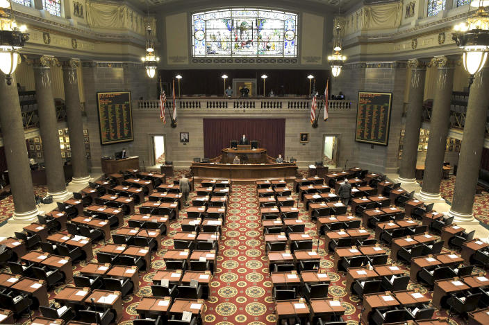FILE In this April 8, 2020, photo provided by the Missouri House of Representatives, shows the House Chamber largely empty as a couple of representatives approach their desks to vote on legislation related to the coronavirus in Jefferson City, Missouri. Some state lawmakers are having to choose between risking their health and carrying out their elected duties amid the coronavirus outbreak. Over the past month, at least 13 states have approved some form of remote voting for lawmakers in at least one of their legislative chambers, but others are pressing ahead with in-person sessions to vote on spending and other hot topics. (Tim Bommel/Missouri House of Representatives via AP)