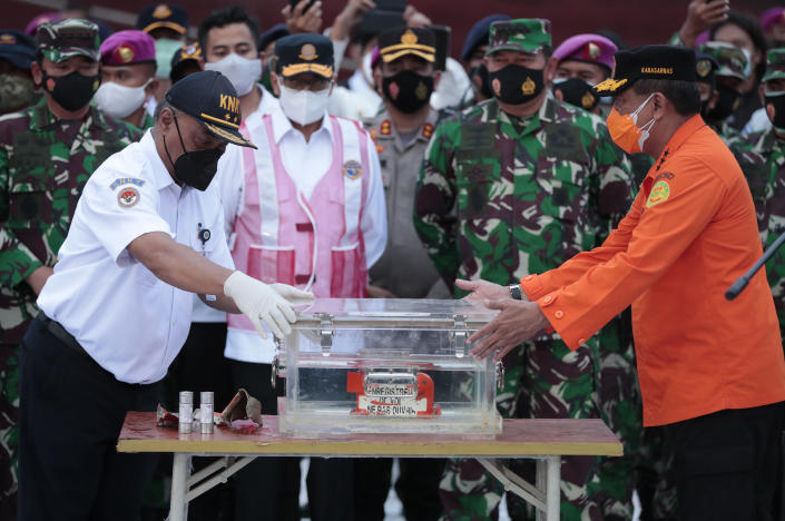 Chief of National Transportation Safety Committee Soerjanto Tjahjono, left, and Chief of National Search and Rescue Agency, Bagus Puruhito, right, hold the box containing the flight data recorder of Sriwijaya Air flight SJ-182 retrieved from the Java Sea where the passenger jet crashed as, rear from left, Armed Forces Chief Mair Marshall Hadi Tjahjanto, Transportation Minister Budi Karya Sumadi, and Navy Chief of Staff Admiral Yudho Margono look on, during a press conference at Tanjung Priok Port, Tuesday, Jan. 12, 2021. Indonesian navy divers searching the ocean floor on Tuesday recovered the flight data recorder from a Sriwijaya Air jet that crashed into the Java Sea with 62 people on board. (AP Photo/Dita Alangkara)