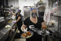 FILE - In this July 1, 2020, file photo, a waitress takes a food order from the kitchen at Slater's 50/50 in Santa Clarita, Calif. Gov. Gavin Newsom announced a new, color-coded process Friday, Aug. 28, 2020, for reopening California businesses amid the coronovirus pandemic that is more gradual than the state's current rules to guard against loosening restrictions too soon. Counties will move through the new, four-tier system based on their number of cases and percentage of positive tests. It will rely on those two metrics to determine a tier: case rates and the percentage of positive tests. (AP Photo/Marcio Jose Sanchez, File)