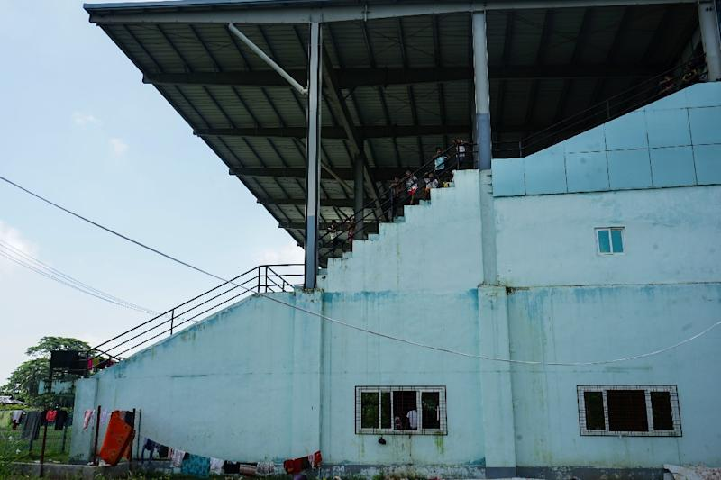 Hundreds of traumatised Hindus now sleep on grubby mats in the overcrowded concourse of a disused football stadium in Sittwe (AFP Photo/AIDAN JONES)