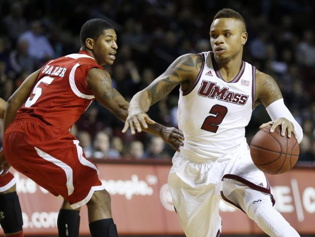 Massachusetts' Derrick Gordon (2) drives past Northern Illinois' Travon Baker (5) in the first half of an NCAA basketball game in Amherst, Mass., Saturday, Dec. 14, 2013. (AP Photo/Michael Dwyer)
