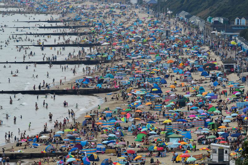 FILE PHOTO: People enjoy Bournemouth Beach during an unusual heat wave in Bournemouth, England