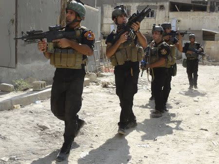 Members of the Iraqi Special Operations Forces (ISOF) conduct a patrol looking for militants of the Islamic State, formerly known as the Islamic State in Iraq and the Levant (ISIL), in a neighbourhood in Ramadi, July 22, 2014. REUTERS/Osama Al-dulaimi