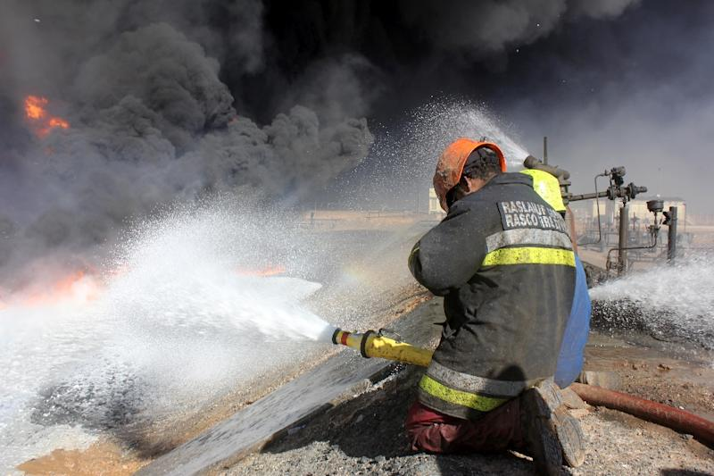A picture taken on January 5, 2016 shows a firefighter working in front of a petroleum storage tank burning at Al-Sidra oil terminal, near Ras Lanouf (AFP Photo/)