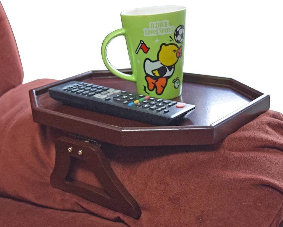 """Perfectfor that side where there's zero space to squeeze in a side table for your beverages and the remote.<br /><br /><strong><a href=""""https://www.amazon.com/Wooden-Armrest-Organizer-Romote-Cherry/dp/B013B74U5O?&linkCode=ll1&tag=huffpost-bfsyndication-20&linkId=f084cac85568c87fc063bc158d61e695&language=en_US&ref_=as_li_ss_tl"""" target=""""_blank"""" rel=""""noopener noreferrer"""">Get it from Amazon for $24.99+ (available in two colors).</a></strong>"""