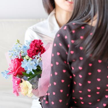 Woman-presenting-another-woman-with-a-bouquet-of-flowers_web