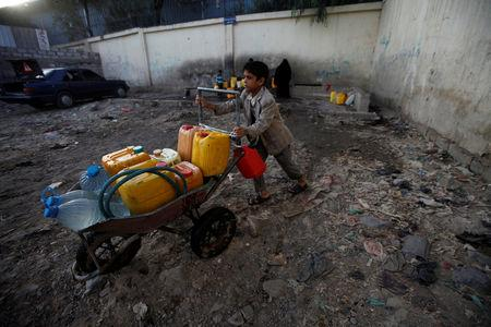 FILE PHOTO: A boy pushes a wheelbarrow filled with water containers after collecting drinking water from a charity tap, amid a cholera outbreak, in Sanaa